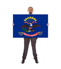 Smiling businessman holding a big card, flag of North Dakota