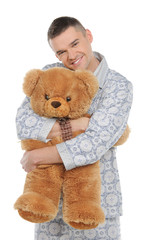 Man with teddy bear. Young man in pajamas hugging teddy bear and