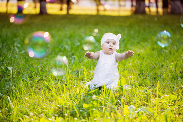 little girl with soap bubble in summer park