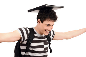 Handsome student smiling balancing a notebook on his head.