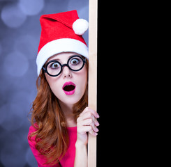 Redhead girl in christmas hat with blackboard
