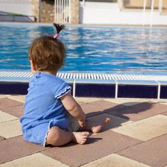 Bebé sentada junto a la piscina