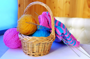 Woollen balls in a small basket with half-knitted sock near it