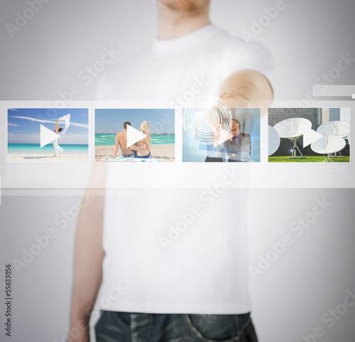 man pressing button on virtual screen