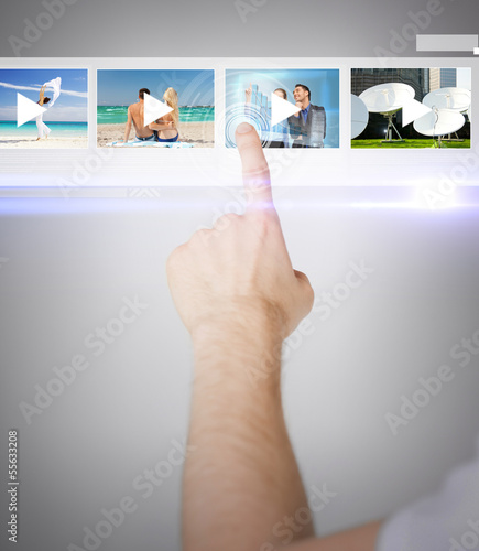 man pressing button on virtual screen
