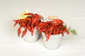 two small pails full of small lobsters with lemon