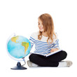 child looking at globe and holding book