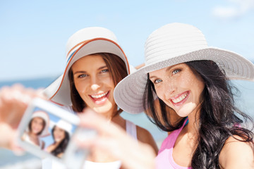 girls taking self portrait on the beach