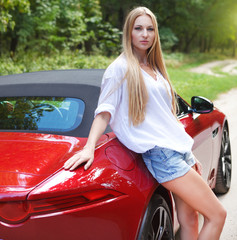 Young woman standing near a  sports car