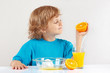 Little cut child makes juice from an orange on white background