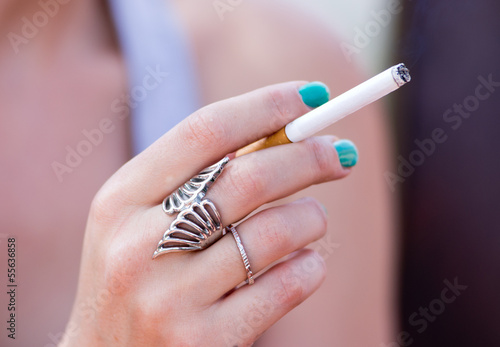 Young girl holds cigarette in her hand