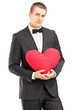 Young handsome man wearing black suit and holding a red heart