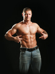 Muscular young man showing abs, isolated on black  background