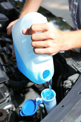Man pours liquid for washing glasses to car
