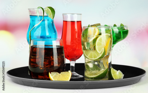 Many glasses of cocktails on tray on table, on bright