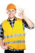 A young construcation worker showing ok