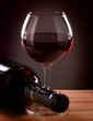 Red wine glass and Bottle on a wooden table