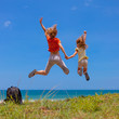 mother and  daughter jumping at the beach