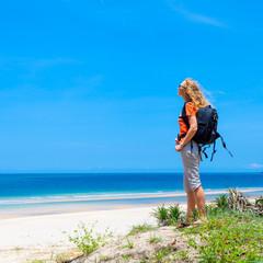 Beautiful  woman standing on the beach enjoying the sun