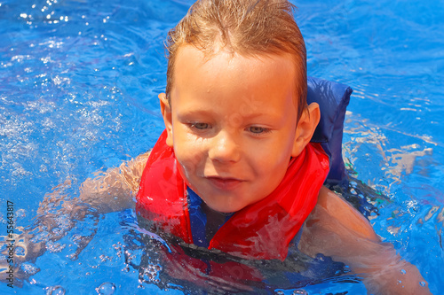 Enthusiastic kid in vest at the pool water park