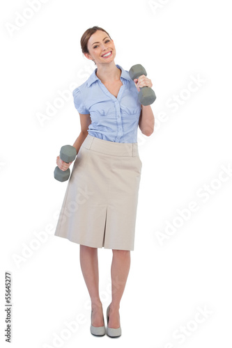 Happy businesswoman lifting dumbbells looking at camera