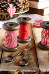 Decoration with wooden spools and red ribbons