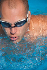 Man in pool with swimming goggles