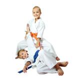 Cheerful kids athletes in kimono doing throws