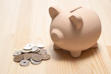 豚の貯金箱と複数の硬貨