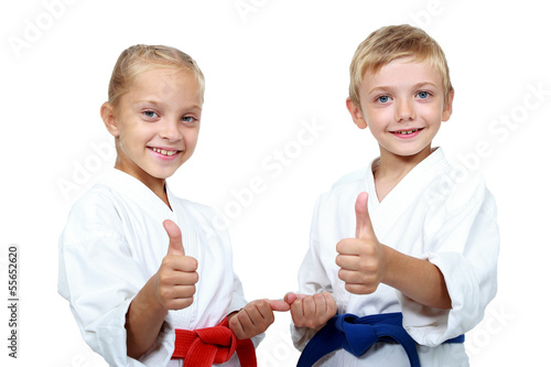 Fotobehang Vechtsporten Children athletes with belts show a thumbs up