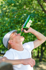 Addicted middle-aged man drinking white wine
