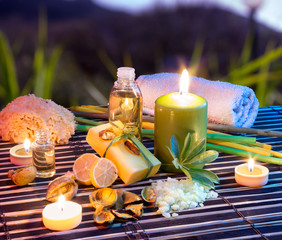 lemon soap , oil, towel, salt and candles in garden