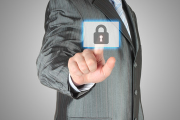 Businessman pushing virtual security button on grey background.