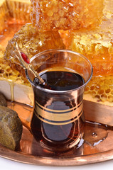 fresh  honeycombs  and wooden stick ,cup of Turkish tea,