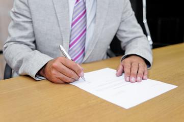 Uomo d'affari che firma un modulo cartaceo