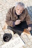 Tramp. Depressed senior man in dirty wear sitting on the floor o poster