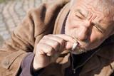 Tramp. Top view of depressed senior man smoking poster