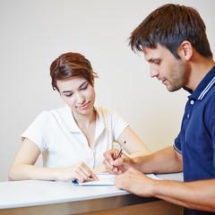 Mann füllt Patientenformular beim Arzt aus
