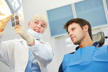 Zahnarzt zeigt Patient Karies auf Röntgenbild