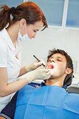 Zahnarzthelferin untersucht Mann beim Zahnarzt