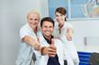 Leinwandbild Motiv Zahnarzt und Team halten Daumen hoch