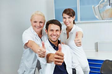 Zahnarzt und Team halten Daumen hoch