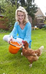 Frau füttert Huhn