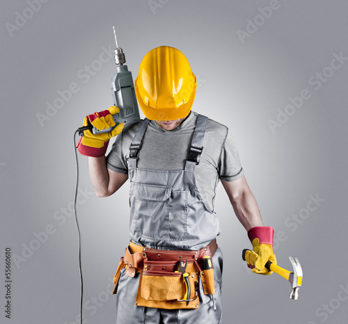 builder in a helmet with a hammer and a drill