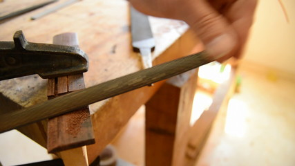 Close up of luthier sanding a guitar piece in workplace