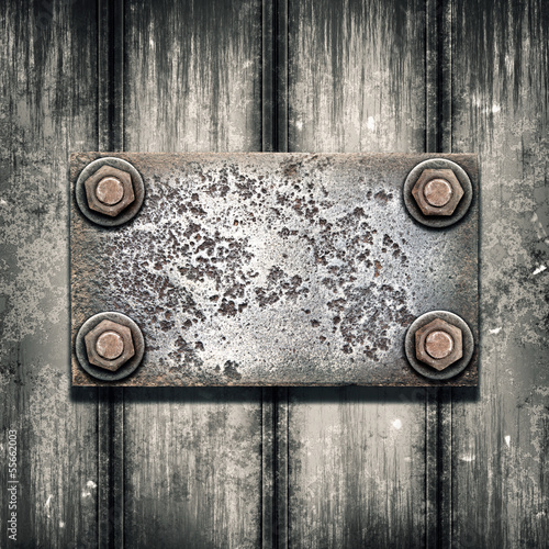 Old metal plate on metallic wall