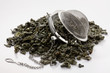 Green tea leaves and a tea strainer on white background