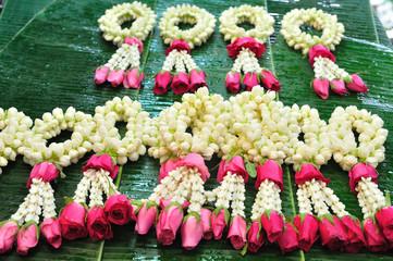 Close up jasmine garland with pink rose on banana leaf.