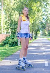 Pretty young woman on roller skates in the park