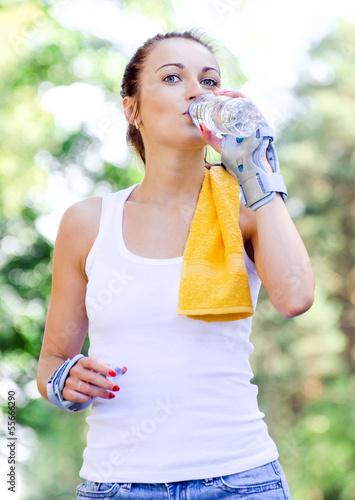Female skater drinking water after training